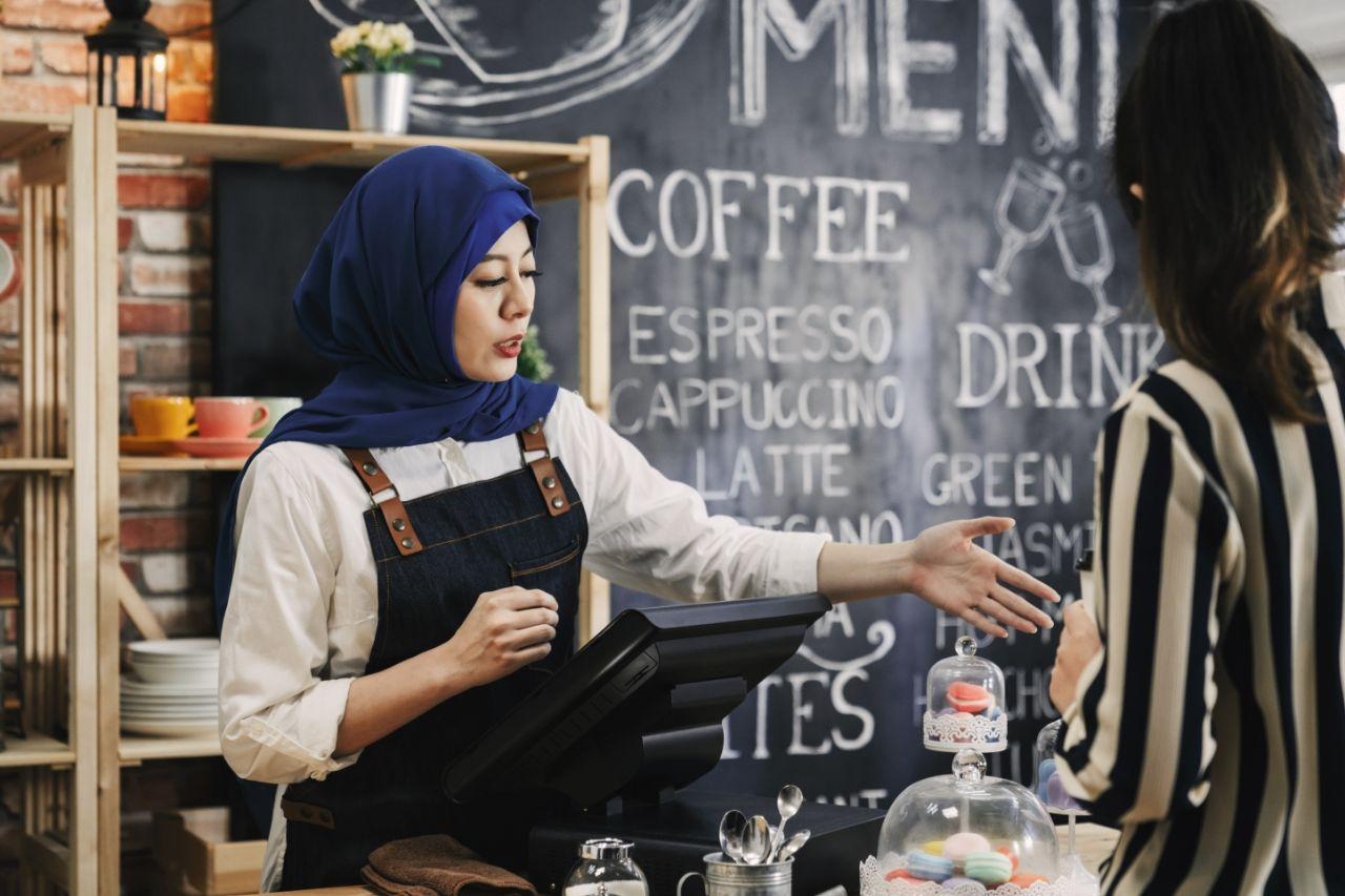 A girl barista talking to customer