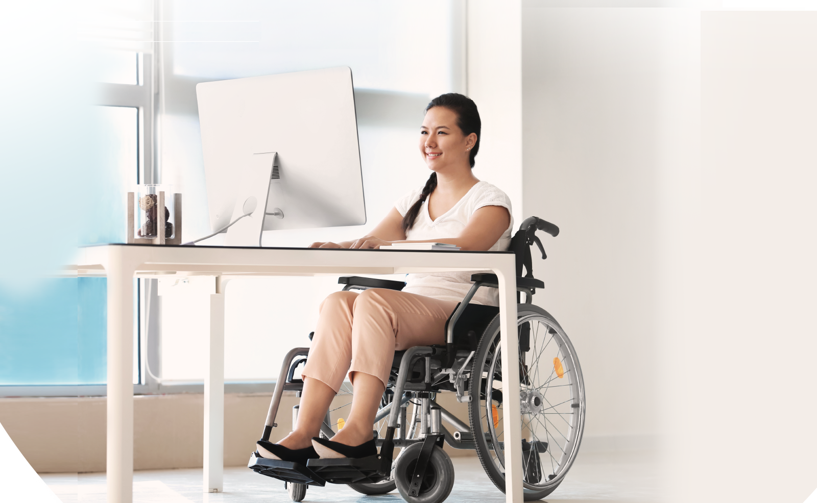 Illustrative image of a person on wheelchair looking at a computer screen